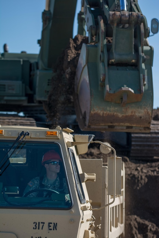 A soldier from the 317th Engineer Company watches his mirrors as a Hydraulic Excavator (HYEX) swings a bucket full of dirt over the back of his M1157 A1P2 10-Ton dump truck. The soldier is taking part in the Blackfeet Innovative Readiness Training (IRT) project. The IRT project produces military readiness while simultaneously providing quality services to communities throughout the U.S. This particular project takes place on the Blackfeet Reservation in Browning, Montana during the months of June thru August (U.S. Army photo by Staff Sgt. Jason Proseus/released).