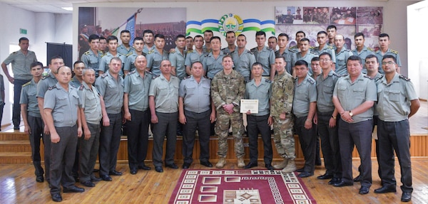 Staff Sgt. Joshua Atanovich, center, and Staff Sgt. William Gordley, center right, both with U.S. Army Central Command's 149th Military Engagement Team, take a final group photo with the Uzbek audience concluding the tactical communications military-to-military engagement June 13-16, 2017, at the Tashkent Institute of Information Technologies in Tashkent, Uzbekistan. (courtesy photo)