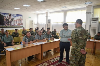 Staff Sgt. William Gordley, 149th Military Engagement Team, right, provided detailed information about the imagery and symbolism of the U.S. Flag during a military-to-military engagement June 15, 2017, at the Tashkent Institute of Information Technologies in Tashkent, Uzbekistan. A U.S. flag shoulder patch was presented to each Uzbek participant. (U.S. Army photo by Staff Sgt. Joshua Atanovich, 149th Military Engagement Team)