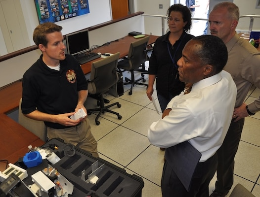 DAHLGREN, Va. (June 15, 2017) - Navy engineer Jonathan Crook briefs visitors about SCAPEGOAT chemical, biological, and radiological (CBR) detection system components during a demonstration. SCAPEGOAT was designed, prototyped, and tested over a six-month period by a team of junior scientists and engineers engaged in the Sly Fox Program at Naval Surface Warfare Center Dahlgren Division. With its relatively low cost and modular interfaces, the SCAPEGOAT system demonstrates the use of emerging technology in meeting warfighter needs.