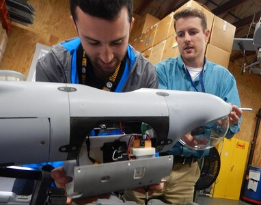 DAHLGREN, Va. (June 15, 2017) - Navy scientist Jordan Lieberman, left, works with engineer Jonathan Crook to install the SCAPEGOAT payload onto a Boeing Insitu Scan Eagle unmanned aerial vehicle (UAV) prior to a system test flight. The SCAPEGOAT system - which includes modular interfaces to multiple chemical, biological, and radiological sensors and UAV platforms - was developed by junior scientists and engineers engaged in the Naval Surface Warfare Center Dahlgren Division sponsored Sly Fox Program over a six-month period.