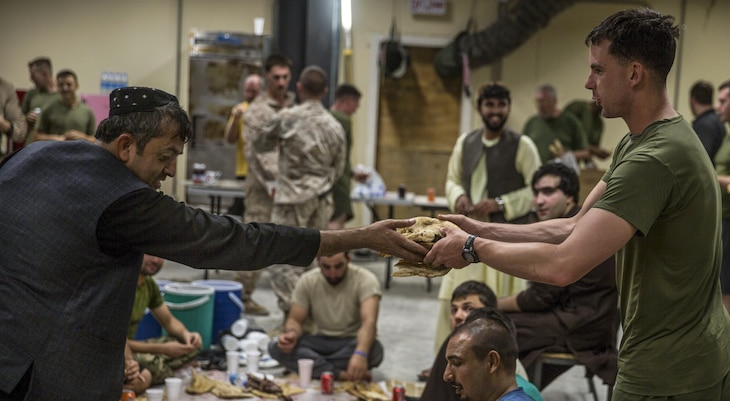 This image shows an Afghan passing goat and bread to a Marine during a feast in Afghanistan.