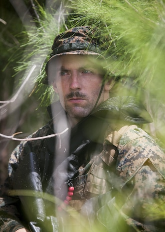 MARINE CORPS TRAINING AREA BELLOWS - Cpl. Ryan Ehlers, a radio reconnaissance team operator with Radio Reconnaissance Platoon, 3rd Radio Battalion posts security during an exercise aboard Marine Corps Training Area Bellows, June 15, 2017. After a two kilometer swim, Ehlers and his team took turns providing security while the others packed away their fins and changed into dry uniforms. (U.S. Marine Corps photo by Lance Cpl. Luke Kuennen)