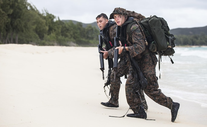 MARINE CORPS TRAINING AREA BELLOWS – (From front to back) Cpl. Kyle Smith alongside Cpl. Samuel Perry, both radio reconnaissance team operators with Radio Reconnaissance Platoon, 3rd Radio Battalion, walk onto a beach after swimming two kilometers in the Pacific Ocean during a Radio Reconnaissance Operator's Course aboard Marine Corps Training Area Bellows, June 15, 2017. For 13 weeks, Marines conducted the Radio Reconnaissance Operator's Course utilizing various training areas to push the students past their physical and mental limits to prepare themselves when they embed with a reconnaissance platoon. (U.S. Marine Corps photo by Cpl. Jesus Sepulveda Torres)