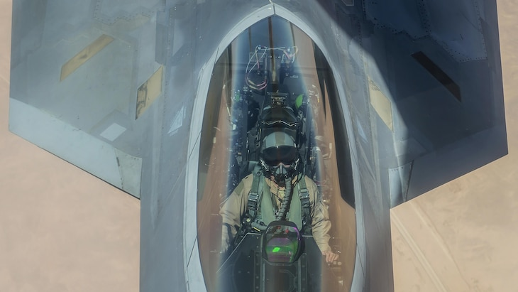 This image is an overhead shot of a pilot in the cockpit of a fighter jet.