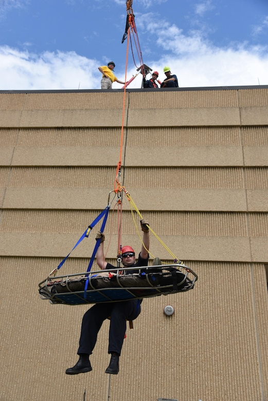 """Robert Hornsby, Biloxi Firefighter, balances himself while being raised from the bottom of the Weather Training Complex with a """"victim"""" during rope rescue operations training June 14, 2017, on Keesler Air Force Base, Miss. Keesler hosted the advanced rescue certification training course, which consisted of confined space rescue, high and low angle rescue and stokes basket rescue operations, for Keesler and Biloxi Firefighters. (U.S. Air Force photo by Kemberly Groue)"""