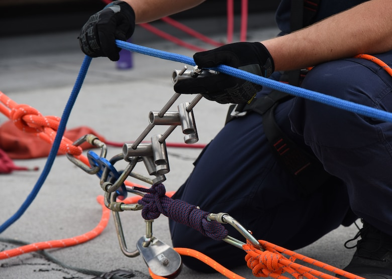Taylor Beesley, Biloxi Firefighter, secures a rope for a controlled descent exercise atop of the Weather Training Complex during rope rescue operations training June 14, 2017, on Keesler Air Force Base, Miss. Keesler hosted the advanced rescue certification training course, which consisted of confined space rescue, high and low angle rescue and stokes basket rescue operations, for Keesler and Biloxi Firefighters. (U.S. Air Force photo by Kemberly Groue)