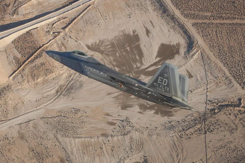 An F-22 Raptor assigned to the 411th Flight Test Squadron maneuvers over the Mojave Desert during a test mission. The 411th Flight Test Squadron's quick integration of MGRS interface software enabled the Raptor to effectively engage ISIS targets in Syria. (Photo by Chad Bellay/Lockheed Martin)