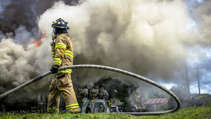 This image shows a firefighter holding a hose with smoke in the background.