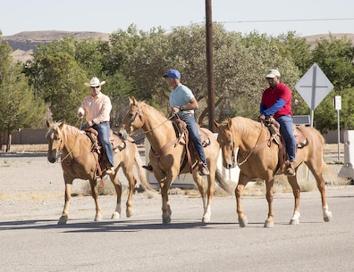 Col. Sekou S. Karega (right), commanding officer, MCLB Barstow,Terry Holladay, trainer, and base Sgt. Maj. Segio MartinesRuiz take an easy ride on Iwo Jima St. in preparration for the upcoming Cody Stampede and Rodeo scheduled for July 4 in Cody, Wyo.