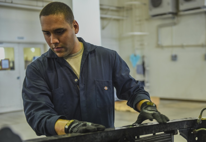 U.S. Air Force Airman 1st Class Kenneth Velez, 18th Mission Support Group vehicle maintainer, replaces parts on an 18th Security Forces Squadron truck in the vehicle maintenance shop June 21, 2017, at Kadena Air Base, Japan. Vehicle maintainers work on several different types of government vehicles, such as 18th SFS patrol cars and 18th Logistics Readiness Squadron buses. (U.S. Air Force photo by Senior Airman Nick Emerick)