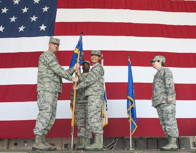 Col. Joann V. Palmer, 8th Medical Group commander, receives the guidon from Col. David Shoemaker, 8th Fighter Wing commander, during a change of command ceremony at Kunsan Air Base, Republic of Korea, June 23, 2017. Shoemaker presided over the ceremony in which Col. Lisa A. Davison relinquished command of the 8th MDG to Palmer. (U.S. Air Force photo by Senior Airman Colville McFee/Released)