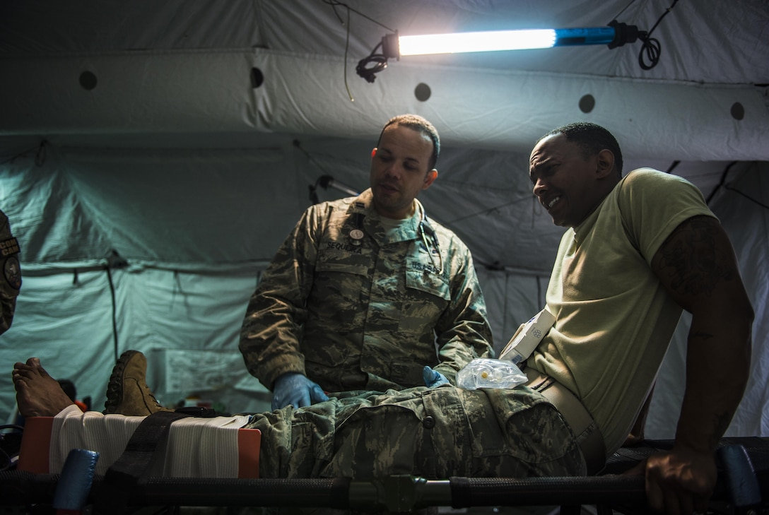 (left) Capt. Ricardo Sequeira, an 821st Contingency Response Squadron flight medicine provider, talks about his medical procedures for a lower leg trauma to Staff Sgt. Zachary Green, Headquarters Air Mobility Command, standardization and evaluation, during a medical exercise at Battle Creek Air National Guard Base, Mich., on June 11, 2017. Turbo Distribution 17-2 is a U.S. Transportation Command exercise designed to assess the Joint Task Force-Port Opening's ability to deliver and distribute cargo during humanitarian and disaster relief operations. (U.S. Air Force photo/Senior Airman Xavier Navarro)