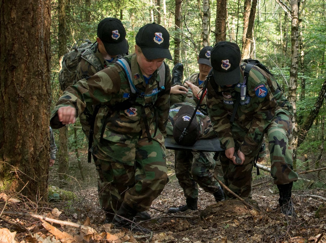 Cadets with the Civil Air Patrol European Encampment carry a stretcher bearing a fellow cadet through a woodland obstacle course on Ramstein Air Base, Germany, June 21, 2017. The cadets spent more than a week living in deployment tents on Ramstein, carrying out physical and mental tasks in a manner somewhat similar to Air Force Basic Training. (U.S. Air Force photo by Senior Airman Elizabeth Baker)