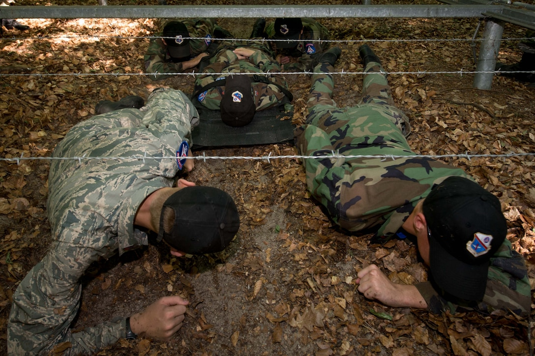 Cadets with the Civil Air Patrol European Encampment pull a simulated patient under barbed wire on a woodland obstacle course on Ramstein Air Base, Germany, June 21, 2017. The encampment curriculum encompasses four core areas: aerospace education, leadership development, character development, and physical fitness. The curriculum designed, in part, to prepare cadets for a possible military aerospace career. (U.S. Air Force photo by Senior Airman Elizabeth Baker)