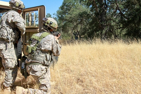 An OPFOR role player surrenders after a simulated firefight with the 341st Military Police Company, 200th Military Police Command at Fort Hunter Liggett, Calif., June 19, 2017. Soldiers from the 341st Military Police Company, 200th Military Police command react to simulated small arms fire during a situational training exercise at Fort Hunter Liggett, Calif., June 19, 2017. More than 3000 U.S. Army Reserve soldiers are participating in the 84th Training Command's Warrior Exercise (WAREX) 19-17-03 at Fort Hunter Liggett, Calif.; the WAREX is a large-scale collective training platform to generate capable, lethal and combat ready forces. U.S. Army photo by Capt. Patrick Cook