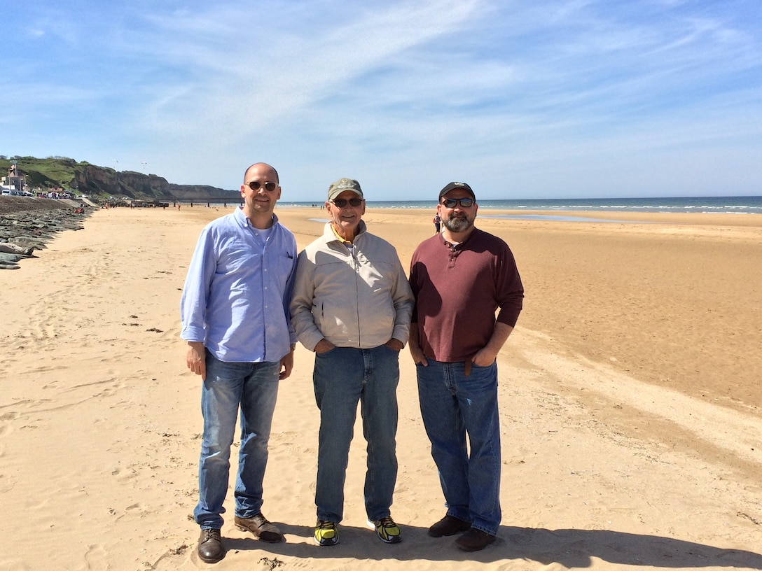 From left, Lt. Col. Christopher Schumann, retired Maj. George Schumann, and Eric Schumann, pose for a group photo at Omaha Beach, France, in May 2017. The retired major was taking his first trip to Europe to visit his son Christopher, 48th Fighter Wing staff judge advocate at RAF Lakenheath. (Courtesy photo)