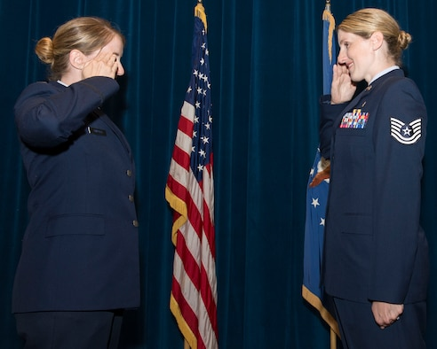 U.S. Air Force Capt. Nicole Tripputi, a contract negotiator with the 645th Aeronautical Systems Group, Big Safari, gives the oath of enlistment to her sister, Tech. Sgt. Jennifer Stem, 88th Aerospace medicine squadron ophthalmic technician, during a re-enlistment ceremony June 19 inside the auditorium of the Wright-Patterson Medical Center at Wright-Patterson Air Force Base. The two have been stationed together at WPAFB for the first time since August 2016.(U.S. Air Force photos/Michelle Gigante)