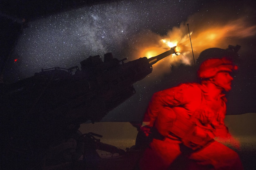 A Marine fires a howitzer in the early morning, creating a yellow flare.