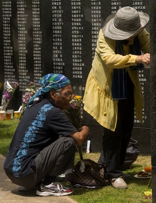 Okinawa residents pay their respects at the Cornerstone of Peace memorial wall during the Okinawa Memorial Day service at Peace Memorial Park, Itoman, Japan, June 23, 2017. The memorial walls are inscribed with more than 240,000 names of people who died in the Battle of Okinawa, regardless of nationality, civilian or military status in the battle. Marine Corps photo by Lance Cpl. Charles Plouffe