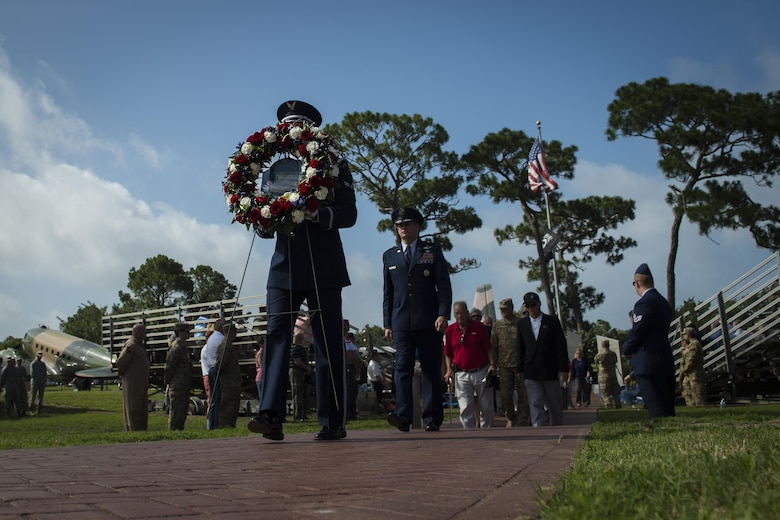 A member of the Hurlburt Field Honor Guard carries a wreath during the Operation Eagle Claw memorial ceremony at Hurlburt Field, Fla., June 23, 2017. Operation Eagle Claw was an attempted hostage-rescue mission in 1980. The mission resulted in five, 8th Special Operations Squadron Airmen and three Marines sacrificing their lives when two of the involved aircraft collided at the Desert One staging site. (U.S. Air Force photo by Airman 1st Class Joseph Pick)