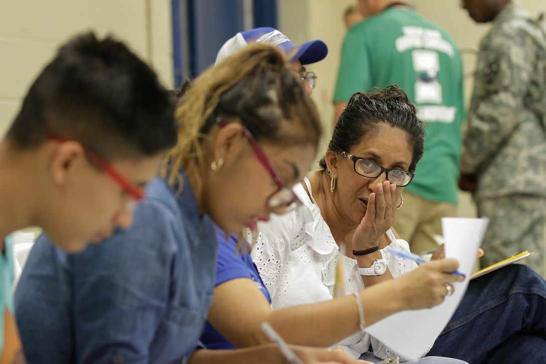 Rosa Torres, a local resident of El Cenizo, Texas, holds her mouth in pain from an abscessed tooth while a translator helps her and her two children fill out the medical intake forms in order for her to receive free dental surgery and her kids to receive eye glasses despite having no insurance during the Joint Texas A&M Colonias Innovative Readiness Training designed to train Soldiers and provide free medical, dental and optometric care to low income residents in the border regions of Web County, Texas 19-29 June 2017. (U.S. Army Reserve photo by Cpt. Joe Bush 215th Mobile Public Affairs Detachment.)