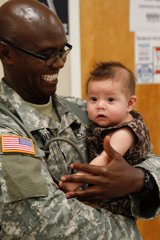 1st Lt. Douglas Ndunga, a U.S. Army Reserve staff nurse assigned to the 7226 Medical Support Unit, Fort Jackson, S.C., holds five-month-old Isaac Russell Deluna, while his mother Jannette, a Resident of El Cenizo, Texas, goes through initial patient screening during the Joint Texas A&M Colonias Innovative Readiness Training designed to train Soldiers and provide free medical, dental and optometric care to low income residents in the border regions of Web County, Texas 19-29 June 2017. (U.S. Army Reserve photo by Cpt. Joe Bush 215th Mobile Public Affairs Detachment.)