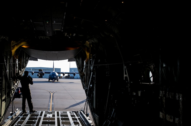 An Airman from the 9th Special Operations Squadron peers out from the back of an aircraft used for a 'fini flight' early in the morning at Cannon Air Force Base, New Mexico, Jun. 9, 2017. Dating back to World War II, the U.S. military has celebrated pilots' and other experienced officers' final flights either at their current unit or their career. Pilots use these celebrations as another opportunity to help train accompanying Airmen on their roles aboard the aircraft to ensure mission readiness. (U.S. Air Force photo by Senior Airman Lane T. Plummer)