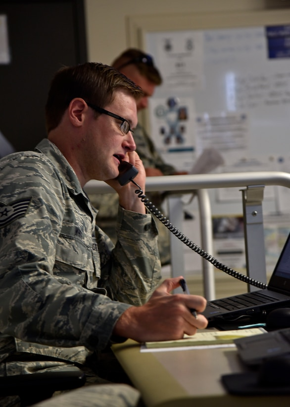 Air Force Technical Sgt. Derek D. White, 175th Wing emergency manager, answers a phone call June 22, 2017, in the emergency operations center at Warfield Air National Guard Base, Middle River, Md. White was contacting units to get full accountability of base Airmen during an active shooter training exercise. (U.S. Air National Guard photo by Airman Sarah M. McClanahan)