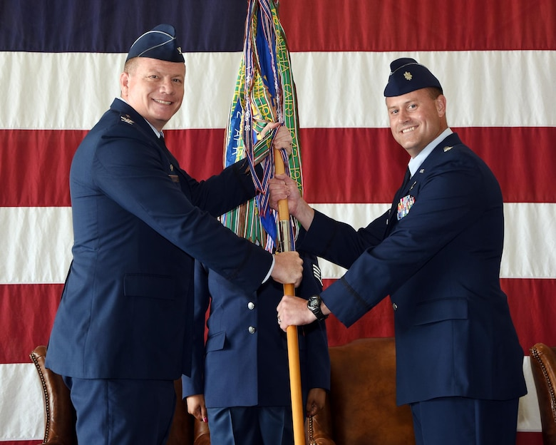 Col. Stan Lawrie, 14th Operations Group Commander, passes the 49th Fighter Training Squadron Guidon to Lt. Col. John Macasek, the new 49th FTS Commander, June 16, 2017, at Columbus Air Force Base, Mississippi. The passing of the guidon has been a military tradition dating back to ancient times. The troops of the old commander would assemble and salute him one last time, then the new commander would receive the guidon, symbolizing he is taking charge of the troops, and the troops would then welcome the new commander. (U.S. Air Force photo by Melissa Doublin)
