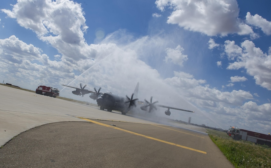 """A MC-130J Commando II is sprayed by firetrucks, known as a """"water salute,"""" as it taxis on the flightline during the 'fini flight' of its pilot, Col. Benjamin Maitre, former 27th Special Operations Wing commander, at Cannon Air Force Base, New Mexico, Jun. 1, 2017. The tradition of spraying plumes of water over aircraft can signal the end of the pilot's career there or mark the beginning or end of the aircraft's life. Dating back to World War II, the U.S. military has celebrated pilots' and other experienced officers' final flights either at their current unit or their career. Pilots use these celebrations as another opportunity to help train accompanying Airmen on their roles aboard the aircraft to ensure mission readiness. (U.S. Air Force photo by Senior Airman Lane T. Plummer)"""
