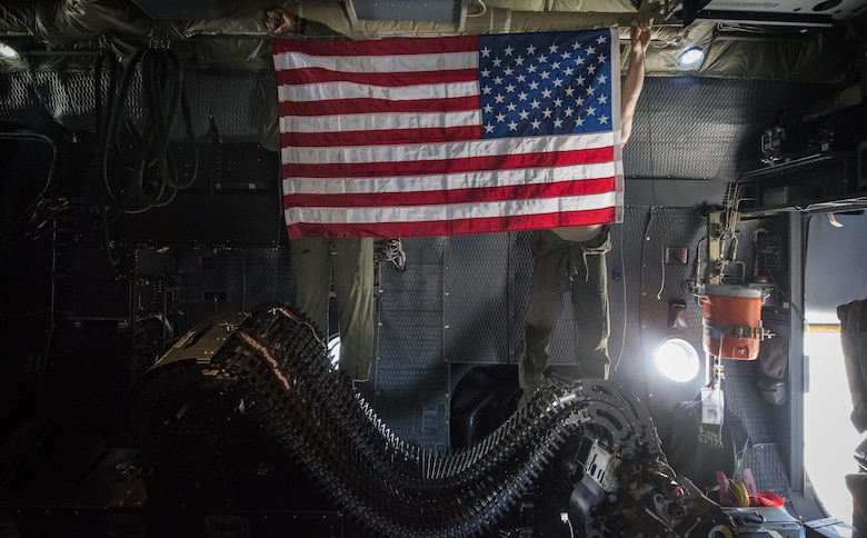 Airmen from the 16th Special Operations Squadron hang up the U.S. flag as they prepare for takeoff during a 'fini flight' at Cannon Air Force Base, New Mexico, Jun. 9, 2017. Dating back to World War II, the U.S. military has celebrated pilots' and other experienced officers' final flights either at their current unit or their career. Pilots use these celebrations as another opportunity to help train accompanying Airmen on their roles aboard the aircraft to ensure mission readiness. (U.S. Air Force photo by Senior Airman Lane T. Plummer)