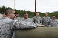 U.S. Air Force Staff Sgt. Michael Ramirez, munitions crew chief with the 3rd Munitions Squadron, explains the process of building a Joint Direct Attack Munition Guided Bomb Unit to Air Force Col. Frank Flores, commander Pacific Air Forces regional support center, and a group of company-grade officers at Joint Base Elmendorf-Richardson, Alaska, June 19, 2017. Bomb builds provide training and certification for 230 personnel within 3rd MUNS and keeps the squadron compliant, lethal and ready.