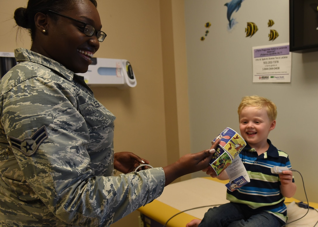 Airman 1st Class Bianca Miller, 19th Medical Operations Squadron pediatric medical technician, gives Reid a sticker after an appointment June 6, 2017, at Little Rock Air Force Base, Ark. The pediatrics clinic is comprised of approximately eight members and sees approximately 90 patients a week. (U.S. Air Force photo by Senior Airman Mercedes Taylor)