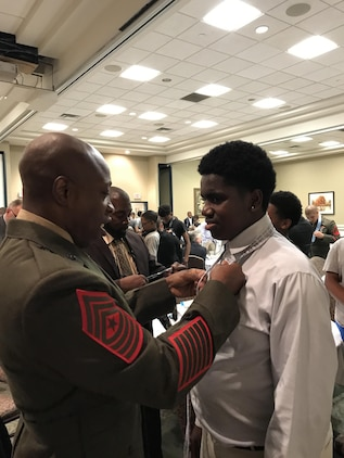 """Marine Corps Logistics Base Albany Sgt. Maj. Johnny L. Higdon, teaches a young man how to properly tie a necktie during the 5th annual """"Ties that Bind"""" event.  A group of Marines took part in """"Ties that Bind,"""" a mentoring event that teaches young boys to tie a necktie while forming bonds with some of the community's most distinguished leaders at the Phoebe Northwest Conference Center in Albany, Ga., June 15.  The annual event, hosted by Phoebe Putney Memorial Hospital's Network of Trust School Health Program, selects 50 boys, mostly from homes without fathers, and pairs them with 50 local men."""