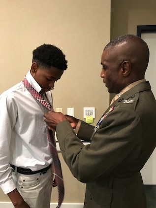 """Col. James C. Carroll III, commanding officer, Marine Corps Logistics Base Albany, teaches a young man how to properly tie a necktie during the 5th annual """"Ties that Bind"""" event.  The mentoring event teaches young boys to tie a necktie while forming bonds with some of the community's most distinguished leaders at the Phoebe Northwest Conference Center in Albany, Ga., June 15.  The annual event, hosted by Phoebe Putney Memorial Hospital's Network of Trust School Health Program, selects 50 boys, mostly from homes without fathers, and pairs them with 50 local men."""