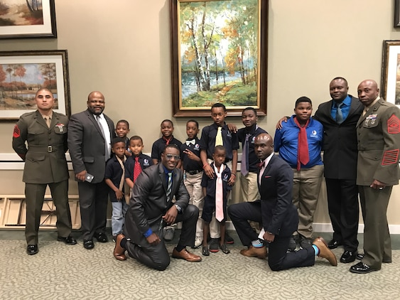 """A group of Marines took part in """"Ties that Bind,"""" a mentoring event that teaches young boys to tie a necktie, while forming bonds with some of the community's most distinguished leaders at the Phoebe Northwest Conference Center in Albany, Ga., June 15.  The annual event, hosted by Phoebe Putney Memorial Hospital's Network of Trust School Health Program, selects 50 boys, mostly from homes without fathers, and pairs them with 50 local men."""