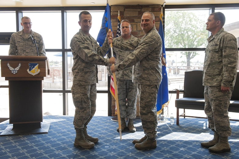Col. Houston R. Cantwell, 49th Wing commander, takes the 49th Medical Group guidon from Col. Paul A. Willingham, 49th MDG outgoing commander, during a change of command ceremony at Club Holloman, June 23, 2017. During the ceremony, Willingham relinquished command of the 49th MDG to Col. Paul R. Brezinski. (U.S. Air Force photo by Airman 1st Class Ilyana A. Escalona)