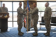 Col. Houston R. Cantwell, 49th Wing commander, gives the 49th Medical Group guidon to Col. Paul R. Brezinski during a change of command ceremony at Club Holloman, June 23, 2017. During the ceremony, Col. Paul R. Brezinski took command of the 49th MDG from Col. Paul A. Willingham, 49th MDG outgoing commander. (U.S. Air Force photo by Airman 1st Class Ilyana A. Escalona)