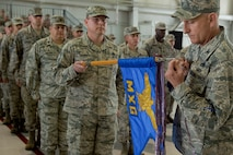 U.S. Air Force Col. Todd Andre, 1st Maintenance Group commander, hangs a streamer for a meritorious unit award during the 1st Fighter Wing Change of Command ceremony at Joint Base Langley-Eustis, Va., June 23, 2017. U.S. Air Force Col. Peter Fesler relinquished command after two years of service. (U.S. Air Force photo/Senior Airman Derek Seifert)