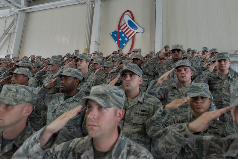 Airmen of Joint Base Langley-Eustis, Va. render a salute during the national anthem at the 1st Fighter Wing change of command, June 23, 2017. At the change of command U.S. Air Force Col. Peter Fesler relinquished command to U.S. Air Force Col. Jason Hinds. (U.S. Air Force photo/Staff Sgt. Carlin Leslie)
