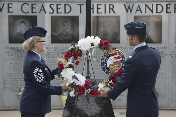 U.S. Air Force Col. Paul Moga, 33rd Fighter Wing commander, right, and Chief Master Sgt. Shelley Cohen, 307th Bomb Wing command chief, place a wreath in front of the burning sword during the Khobar Towers 21st Anniversary Wreath Laying Ceremony June 23, 2017, at Eglin Air Force Base, Florida. On June 25, 1996, a bomb was detonated near the Khobar Towers housing complex in Dhahran, Saudi Arabia. Nineteen Airmen were killed and more than 400 U.S. and international military and civilians were injured in the blast.  Of the 19 killed, 12 were Nomads. Each year the 33 FW holds a ceremony in remembrance of that day. (U.S. Air Force photo by Staff Sgt. Peter Thompson)