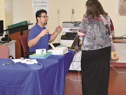 Chris Solano, a human resources officer at Fort Riley's Civilian Personnel Advisory Center, answers a question for an applicant at a Fort Riley Child care Provider Hiring Event June 13 at Parent Central 6620 Normandy Drive at Fort Riley. The event yielded 30 interviews and 29 tentative job offers – 25 of which were to military spouses or dependents — all of which were accepted.
