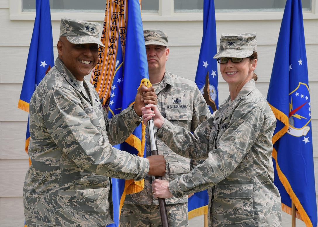 Major General Anthony Cotton, 20th Air Force Commander, passes the guidon to Col. Stacy Huser, 90th Missile Wing commander, during the change of command ceremony on the Argonne Parade Field at F.E. Warren Air Force Base, Wyo., June 23, 2017. The ceremony signified the transition of command from Col. Stephen Kravitsky to Huser. (U.S. Air Force photo by Glenn S. Robertson)