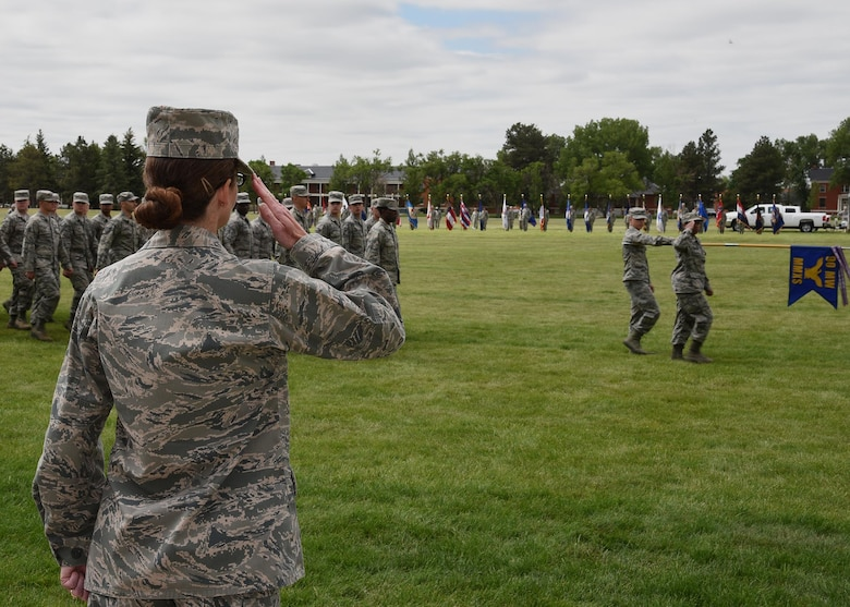 Colonel Stacy Huser, 90th Missile Wing commander, returns the salute to Airmen from the 90th Missile Maintenance Squadron marching during the Pass in Review at the change of command ceremony on the Argonne Parade Field at F.E. Warren Air Force Base, Wyo., June 23, 2017. The pass in review is a long-standing military tradition that began as a way for a newly assigned commander to inspect his troops. (U.S. Air Force photo by Glenn S. Robertson)
