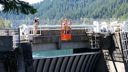 A pair of inspectors dangle high above the spillway of Cougar Dam in a crane bucket, while another Portland District teammate directs the crane operator, May 24. This team of geotechnical, geological, hydraulic, structural and mechanical engineers examined the dam during the periodic inspection, which happens every five years.