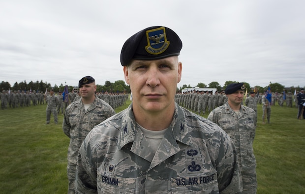 Colonel John Grimm, 90th Security Forces Group commander, stands at parade rest with his group's formation during the 90th Missile Wing change of command ceremony on the Argonne Parade Field at F.E. Warren Air Force Base, Wyo., June 23, 2017. Grimm leads four squadrons responsible for defending the installation which supports more than 7,000 personnel, a weapons storage area and 150 Minuteman III ICBMs and their related infrastructure spread throughout a 9,600 square-mile area across Wyo., Neb., and Colo. The change of command ceremony signified the transition of command from Col. Stephen Kravitsky to Col. Stacy Huser. (U.S. Air Force photo by Staff Sgt. Christopher Ruano)