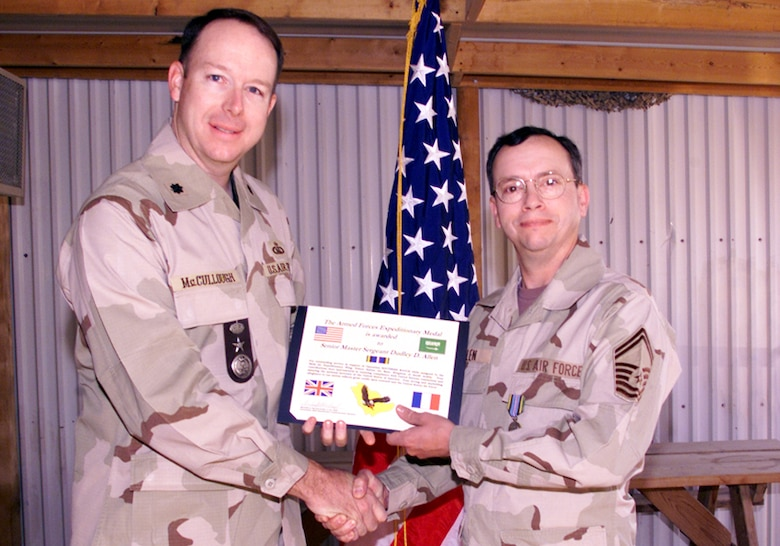 Lt. Col. McCullough presents Senior Master Sgt. Dudley Allen with an Armed Forces Expeditionary Medal certificate for his achievements during Operation Southern Watch in 2000.