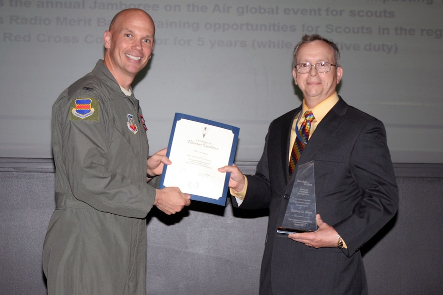 Col. Michael Manion, 55th Wing commander, presents Dudley Allen, 55th Force Support Squadron management analyst, with the 2016 Air Force Volunteer Excellence Award during the 55th Wing staff meeting June 12 at the base conference center.