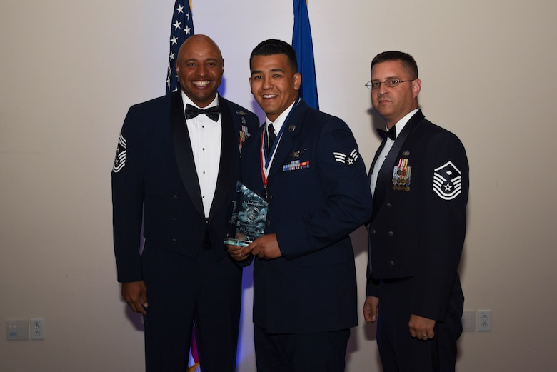 Senior Airman Cristian E. De Leon, 460th Operation Support Squadron staff instructor, receives the Commandant Leadership Award during Airman Leadership School Class 17E graduation June 22, 2017, on Buckley Air Force Base, Colo. This award was earned by displaying all the characteristics of an effective leader. (U.S. Air Force photo by Airman 1st Class Holden S. Faul/ released)